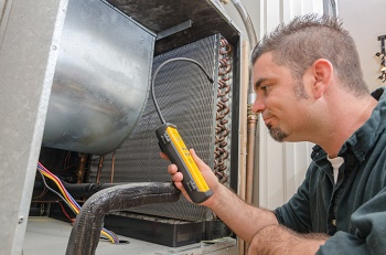 An HVAC technician searches for a refrigerant leak in an air conditioner.